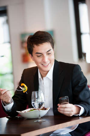 A young and attractive man uses his phone while eating a salad in an indoor restaurant photo