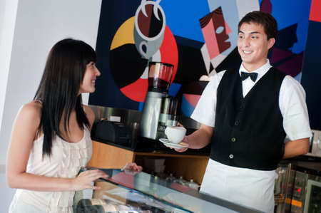 A young and attractive waiter serving coffee to a customer in an indoor restaurant Stock Photo - 5752281