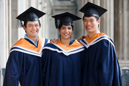 Three young graduates standing in a hallway in graduation attire