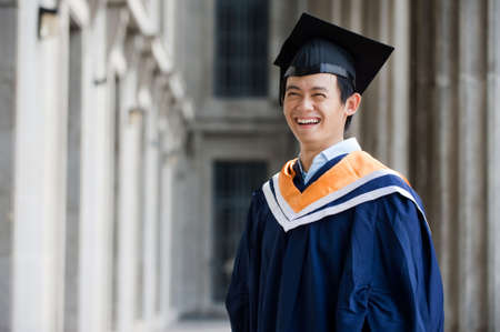 A young graduate in graduation attire standing in a hallway photo