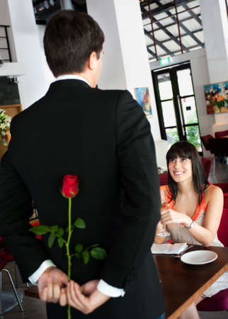 suitor: A young and attractive man holding a rose behind his back to surprise his partner in a restaurant Stock Photo