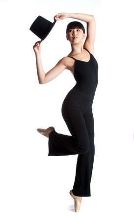 A young asian ballerina dances with a top hat against white background photo