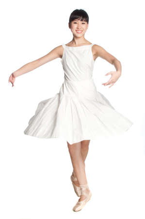 A young asian ballerina does a ballet pose against white background photo