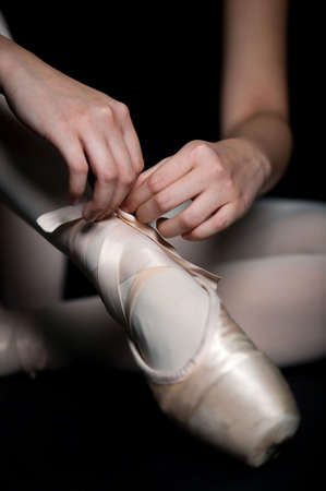 A ballerina tying her ballet slippers on, against black background photo