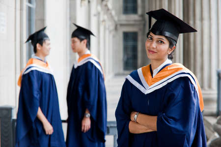 Three young graduates standing outdoors in graduate attire photo