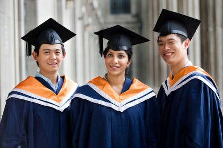 Three young graduates standing in a hallway in graduation attire photo