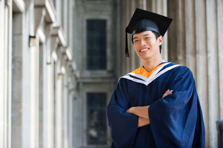 A young graduate in graduation attire standing in a hallway
