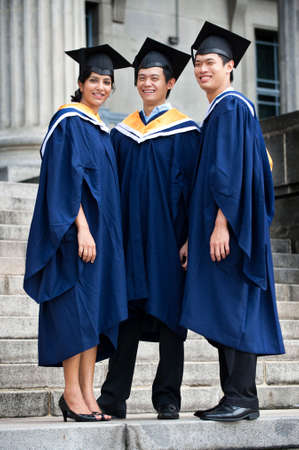 Three young graduates standing outdoors in graduation attire photo