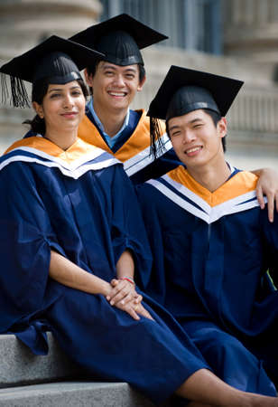 Three young graduates sitting on steps outdoors in graduate attire photo