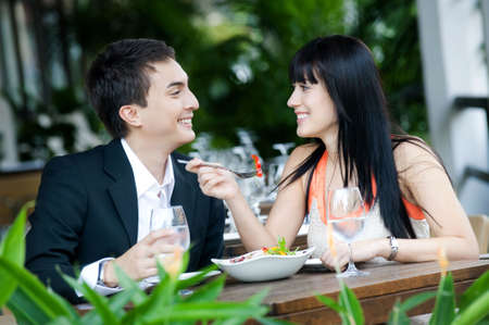 outdoor restaurant: An attractive young couple shares a salad at an outdoor restaurant
