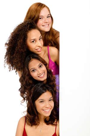 Un grupo de adolescentes con diversas etnias mirando un espacio en blanco contra el fondo blanco
