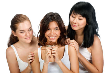 A teenager holding up a cupcake as her two friends look at it over her shoulder, against white background photo