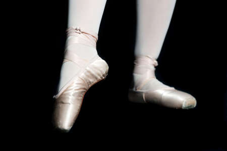 ballet slippers: A pair of feet wearing ballet slippers posing on black background