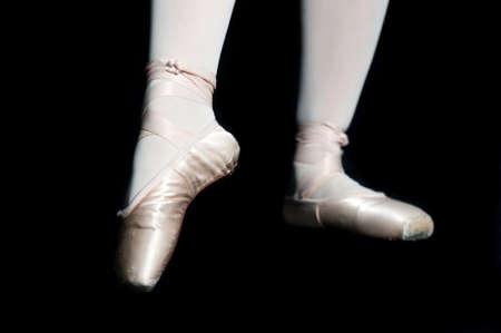 zapatillas ballet: Un par de pies con zapatillas de ballet posando sobre fondo negro Foto de archivo