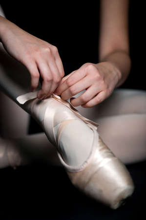 tying: A ballerina tying her ballet slippers on, against black background