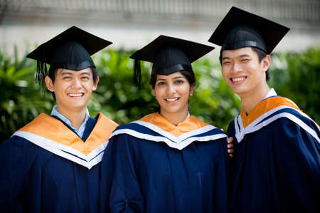 graduation gown: Three young graduates standing outdoors in graduate attire Stock Photo