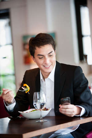 A young and attractive man uses his phone while eating a salad in an indoor restaurant Stock Photo - 5827718