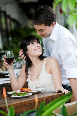 alfresco: A young and attractive woman is surprised by her partner while dining in an outdoor restaurant Stock Photo
