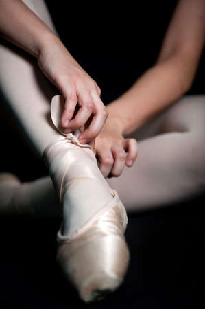 stockings feet: A ballerina tying her ballet slippers on, against black background