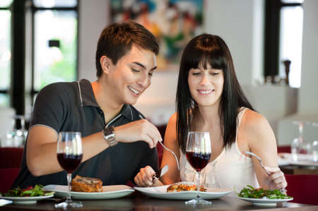 restaurant food: A young and attractive couple dining together in an indoor restaurant