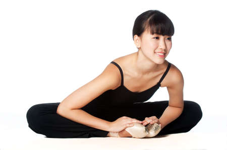A young asian ballerina doing stretches and warm ups against white background Stock Photo - 5883707