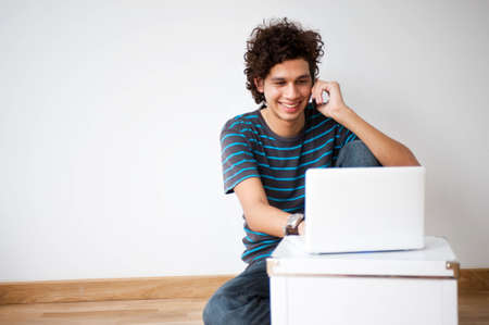 A young and attractive man using his phone and laptop in his new home Stock Photo - 5907072