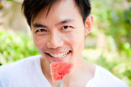 An attractive asian man eating a watermelon outdoors Stock Photo