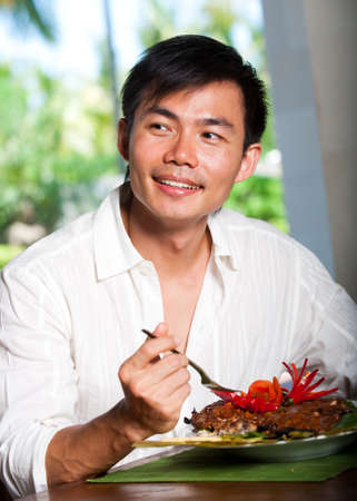 An attractive asian man eating at a restaurant