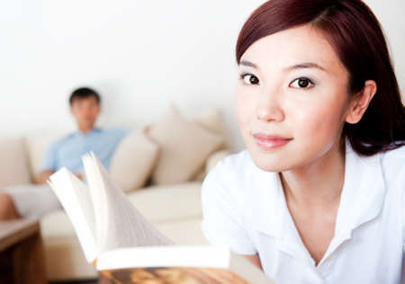 A young attractive Asian couple sitting at home on sofa with coffee and computer