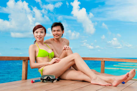 An attractive couple sitting on a wooden boat in the ocean photo