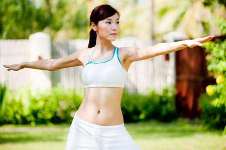 An attractive asian woman practicing yoga outdoors Stock Photo - 5939754