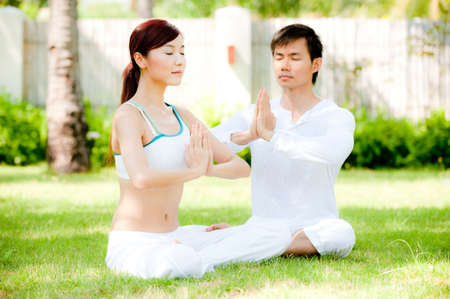 An attractive asian couple practicing yoga outdoors