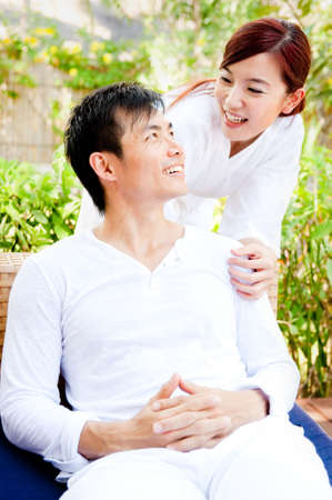 An attractive asian couple relaxing and laughing outdoors