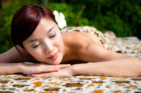An attractive asian woman lying outdoors on a massage table Stock Photo
