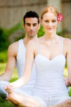 An attractive caucasian couple practicing yoga outdoors