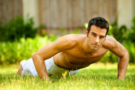 An attractive caucasian man doing a push up outdoors
