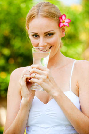 An attractive woman drinking a glass of water outside photo