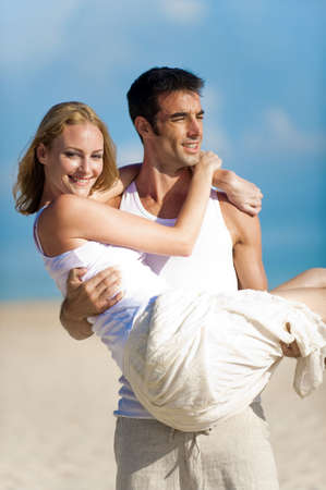 man carrying woman: A good looking couple relaxing by the beach