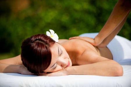A beautiful asian woman getting a massage outdoors Stock Photo