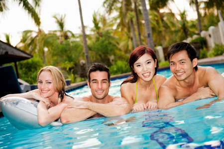 Four attractive asian and caucasian friends having fun in a swimming pool photo