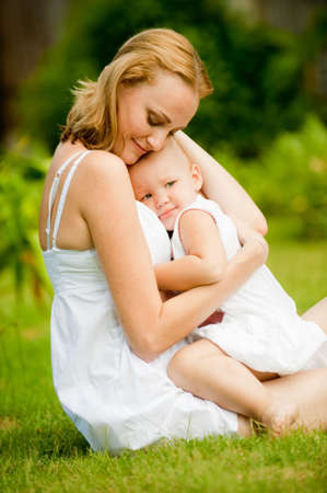 A young caucasian mother holding her child outdoors Stock Photo