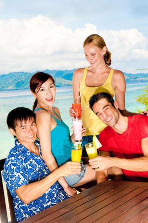 A group of asian and caucasian friends drinking fruit juice by the seaside Stock Photo - 5946711