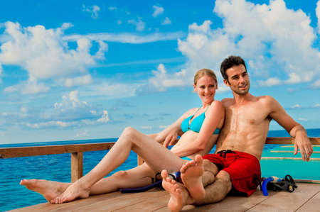 An attractive couple sitting on a wooden boat in the ocean Stock Photo - 5946719