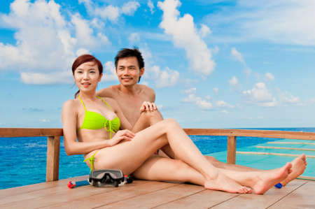 An attractive couple sitting on a wooden boat in the ocean Stock Photo - 5946713