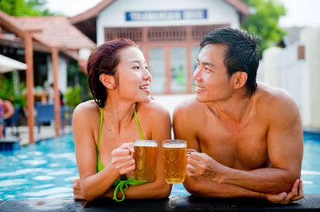 An attractive asian couple clinking beers by the poolside Stock Photo