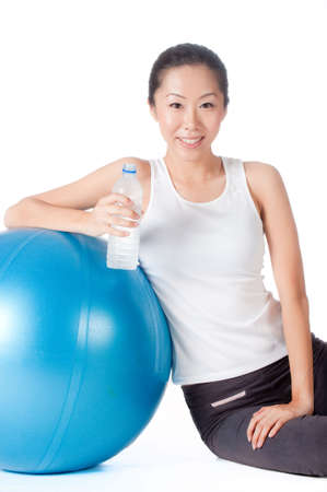 Asian woman with blue yoga ball drinking water on white background