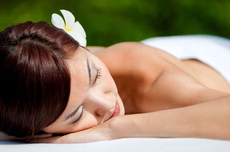 A beautiful asian woman lying down on a massage table outdoors in the sun photo