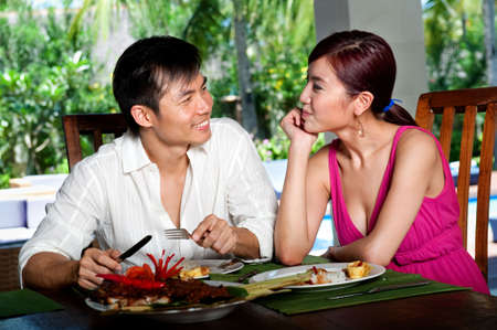 An attractive asian couple eating together at a restaurant Stock Photo