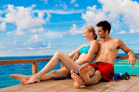 An attractive couple sitting on a wooden boat in the ocean Stock Photo - 5999814