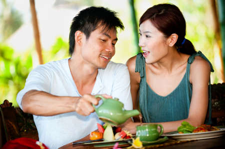 An attractive asian couple eating together at a restaurant photo